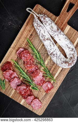 Fuet Salami Wurst Cut In Slices And Whole Sausage On Black Textured Surface, Topview.