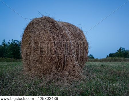 Rural Landscape With One Roll Bale In Field During Blue Hour, Straw Haystack As Cattle Fodder