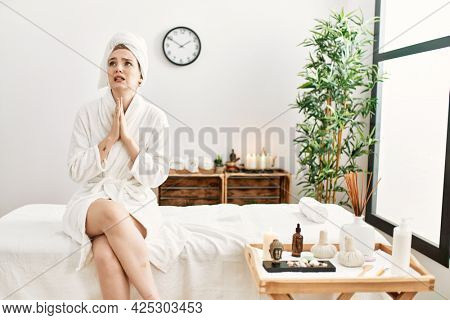 Young blonde woman wearing bathrobe at wellbeing spa begging and praying with hands together with hope expression on face very emotional and worried. begging.