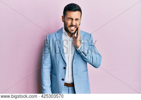 Young hispanic businessman wearing business jacket touching mouth with hand with painful expression because of toothache or dental illness on teeth. dentist