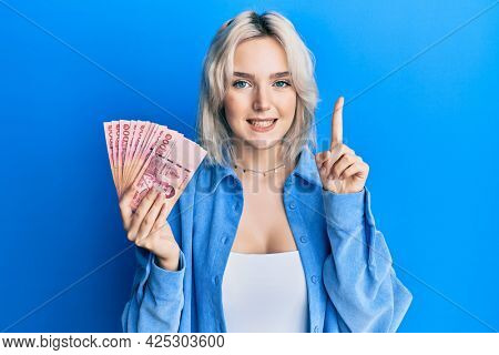 Young blonde girl holding thai baht banknotes smiling with an idea or question pointing finger with happy face, number one