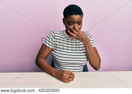 Young african american woman wearing casual clothes sitting on the table smelling something stinky and disgusting, intolerable smell, holding breath with fingers on nose. bad smell