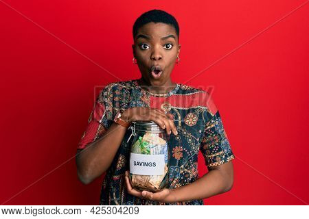 Young african american woman holding savings jar with south african rands money afraid and shocked with surprise and amazed expression, fear and excited face.