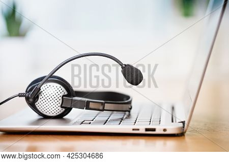 Laptop With Headphones Or Headset On White Desk