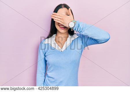 Beautiful woman with blue eyes standing over pink background smiling and laughing with hand on face covering eyes for surprise. blind concept.