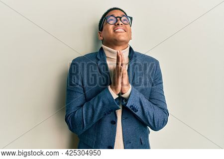 Young handsome hispanic man wearing elegant clothes and glasses begging and praying with hands together with hope expression on face very emotional and worried. begging.