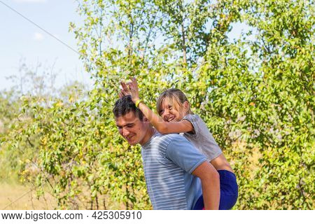 Defocused Brother Giving Sister Ride On Back. Portrait Of Happy Girl With Funny Horns On Man Shoulde