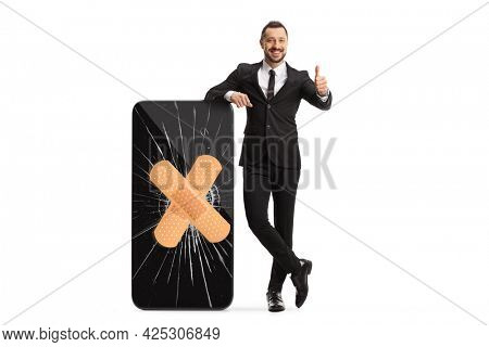 Full length portrait of a salesman and a big smartphone with a broken screen and bandage isolated on white background