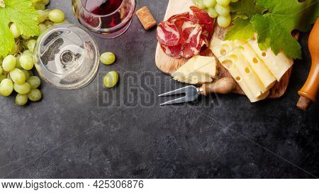 White and red wine glasses, grape and appetizer board with cheese and prosciutto. With copy space. Top view flat lay