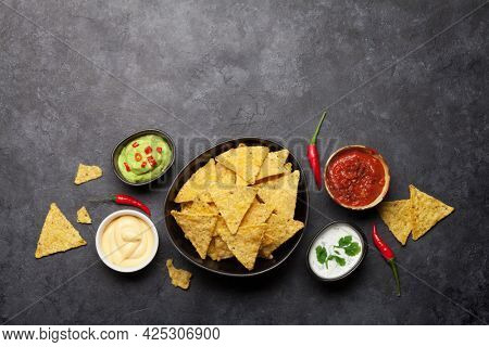 Mexican nachos chips with various sauces - guacamole, salsa, cheese and sour cream. Top view flat lay on stone table with copy space