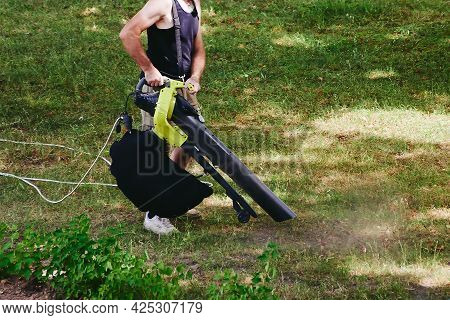 The Worker Blows The Leaves Off The Grass