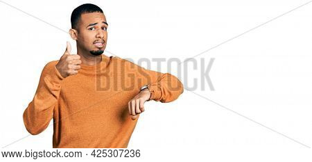 Young african american man wearing casual clothes doing thumbs up and down, disagreement and agreement expression. crazy conflict
