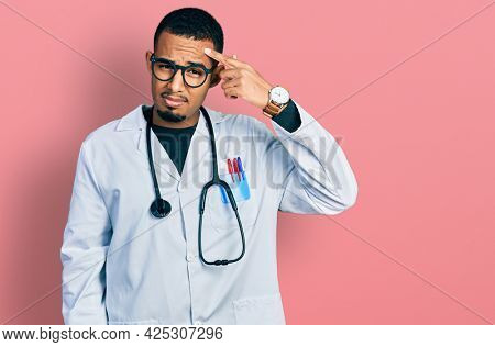 Young african american man wearing doctor uniform and stethoscope pointing unhappy to pimple on forehead, ugly infection of blackhead. acne and skin problem