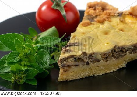 Closeup Wide Studio Shot Of A Slice Of Yellow French Salty Cake, Or Quiche, With Mushrooms On A Blac