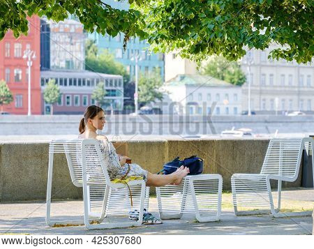 Moscow. Russia. June 26, 2021. A Young Attractive Girl Sits In A Sun Lounger On The Riverfront In Th