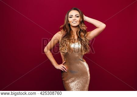 Portrait Of Young Seductive Girl In Golden Dress Touching Her Hair And Looking At Camera Against Red