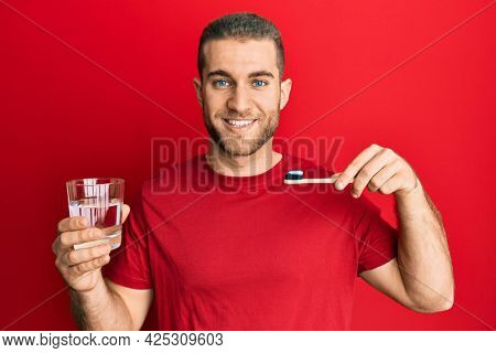 Young caucasian man holding toothbrush with toothpaste smiling with a happy and cool smile on face. showing teeth.