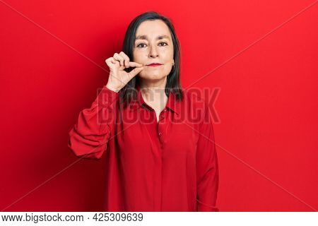 Middle age hispanic woman wearing casual clothes mouth and lips shut as zip with fingers. secret and silent, taboo talking