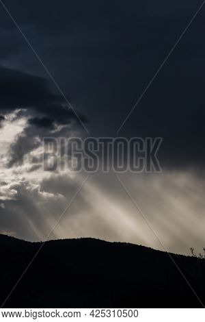 Thick Stormy Clouds Over The Mountains With Intense Sun Rays Peaking Through And Contrasty Light