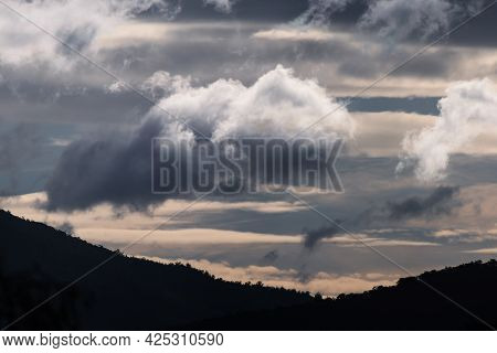 Thick Stormy Clouds Over The Mountains With Intense Sunlight Peaking Through And Contrasty Tones