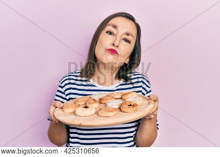 Middle age hispanic woman holding sweet pastries looking at the camera blowing a kiss being lovely and sexy. love expression.