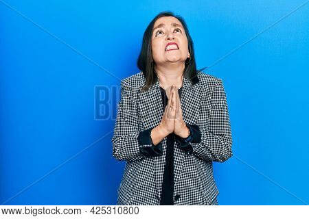 Middle age hispanic woman wearing business clothes begging and praying with hands together with hope expression on face very emotional and worried. begging.