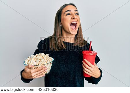 Young brunette girl eating popcorn and drinking soda angry and mad screaming frustrated and furious, shouting with anger looking up.