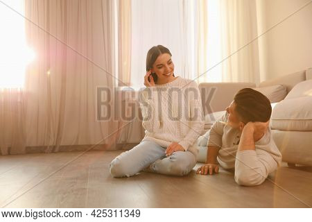 Happy Couple On Warm Floor At Home, Space For Text. Heating System