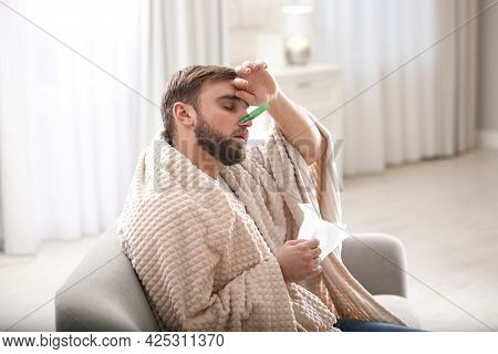 Young Man With Clothespin Suffering From Runny Nose In Living Room