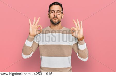 Handsome man with beard wearing casual clothes and glasses relaxed and smiling with eyes closed doing meditation gesture with fingers. yoga concept.