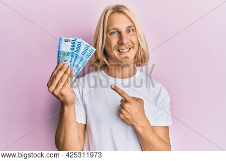 Caucasian young man with long hair holding 1000 hungarian forint banknotes smiling happy pointing with hand and finger