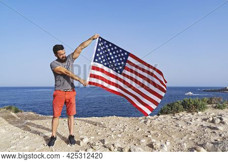 Man Holding Big Waving Usa Flag Outdoor. Independence Day Of United States Of America. Concept Of Am