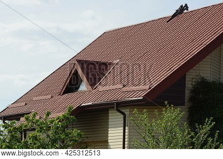 One Attic Window On A Brown Tiled Roof Of A House Against A Gray Sky