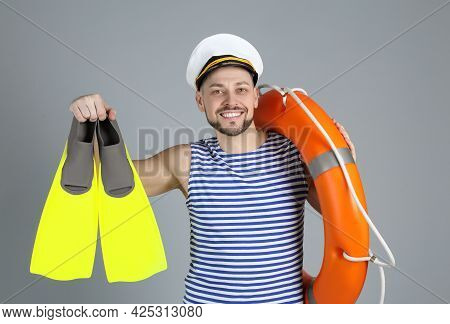 Happy Sailor With Orange Ring Buoy And Swim Fins On Grey Background