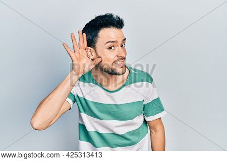 Young hispanic man wearing casual clothes smiling with hand over ear listening an hearing to rumor or gossip. deafness concept.