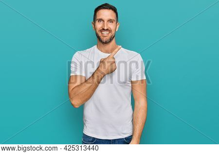 Handsome man with beard wearing casual white t shirt cheerful with a smile of face pointing with hand and finger up to the side with happy and natural expression on face