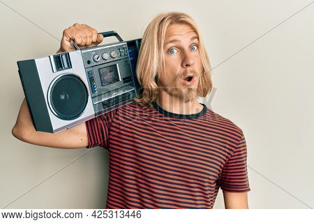 Caucasian young man with long hair holding boombox, listening to music scared and amazed with open mouth for surprise, disbelief face