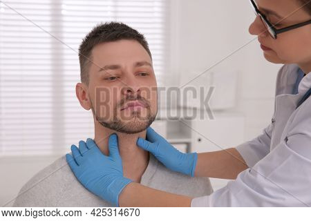 Doctor Examining Thyroid Gland Of Patient In Hospital