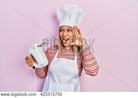 Beautiful hispanic woman holding pastry blender electric mixer shouting and screaming loud to side with hand on mouth. communication concept.
