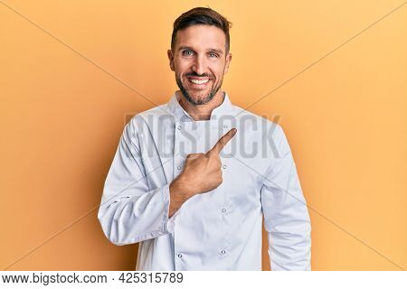 Handsome man with beard wearing professional cook uniform cheerful with a smile of face pointing with hand and finger up to the side with happy and natural expression on face