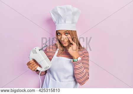 Beautiful hispanic woman holding pastry blender electric mixer pointing to the eye watching you gesture, suspicious expression