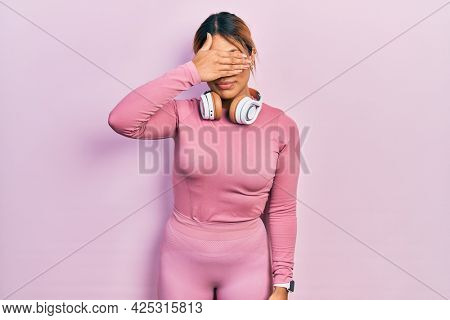 Beautiful hispanic woman wearing gym clothes and using headphones covering eyes with hand, looking serious and sad. sightless, hiding and rejection concept
