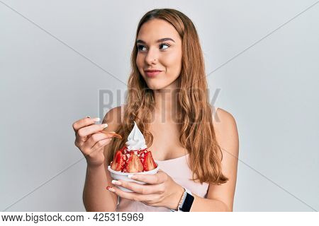 Young blonde woman eating strawberry ice cream smiling looking to the side and staring away thinking.