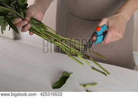 Florist Cutting Stems Of Flowers With Pruner At Workplace, Closeup