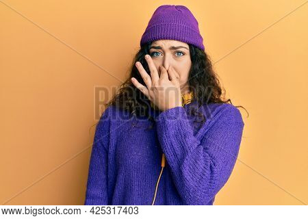 Young brunette woman with curly hair listening to music using headphones smelling something stinky and disgusting, intolerable smell, holding breath with fingers on nose. bad smell