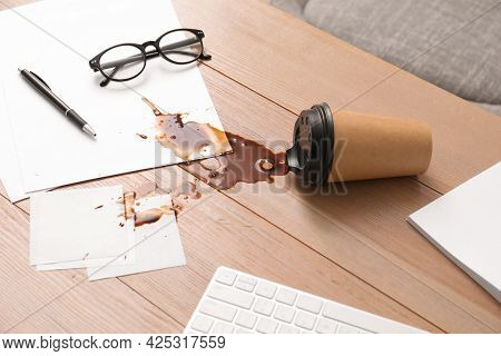 Paper Cup With Coffee Spill On Wooden Office Desk