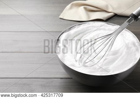 Whipping White Cream With Balloon Whisk On Grey Wooden Table. Space For Text