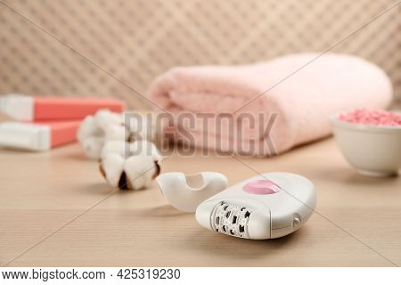 Modern Epilator And Other Hair Removal Products On Wooden Table. Space For Text