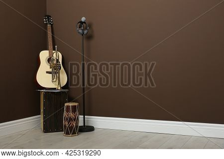 Acoustic Guitar, Trumpet, Hand Drum And Microphone Near Brown Wall Indoors, Space For Text. Musical