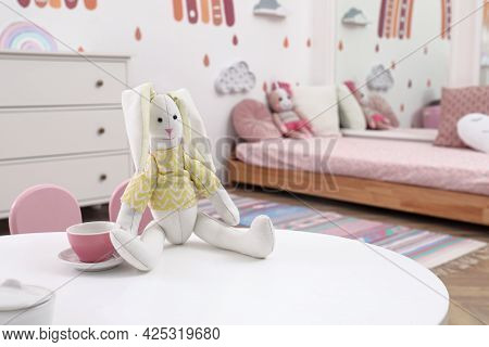 Toy Bunny And Cup On White Table In Child's Bedroom. Montessori Interior